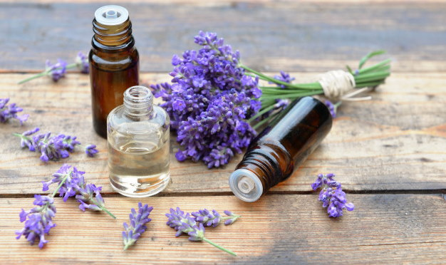 Image of three small essential oil bottles on what in table with a bouquet of purple lavender laying next to them