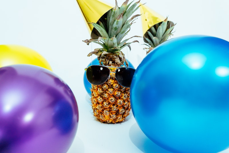Photo of a pineapple wearing sunglasses and a party hat with balloons floating around for a birthday party