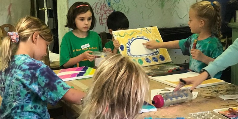 Photo a  children sitting around a table painting and drawing at a art day camp in NJ