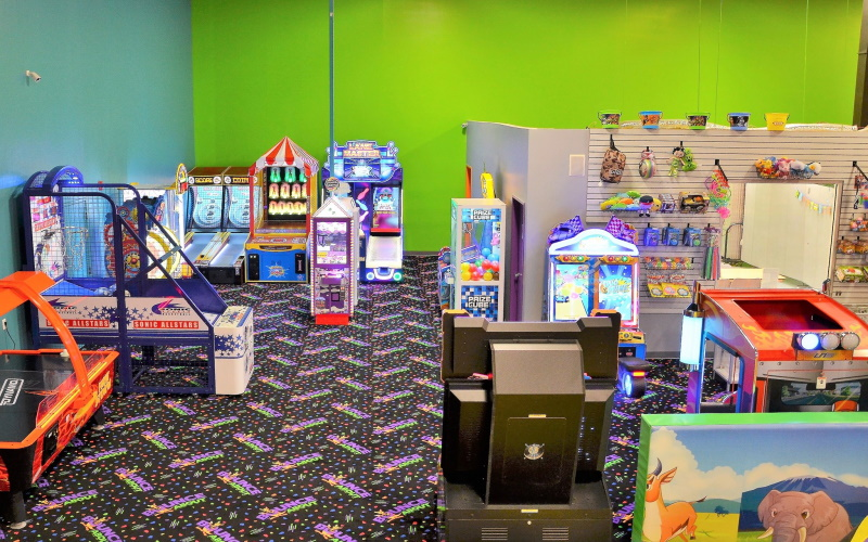 Photo of Bounce About's play room in Toms River Nj with arcade machines and stylized carpet