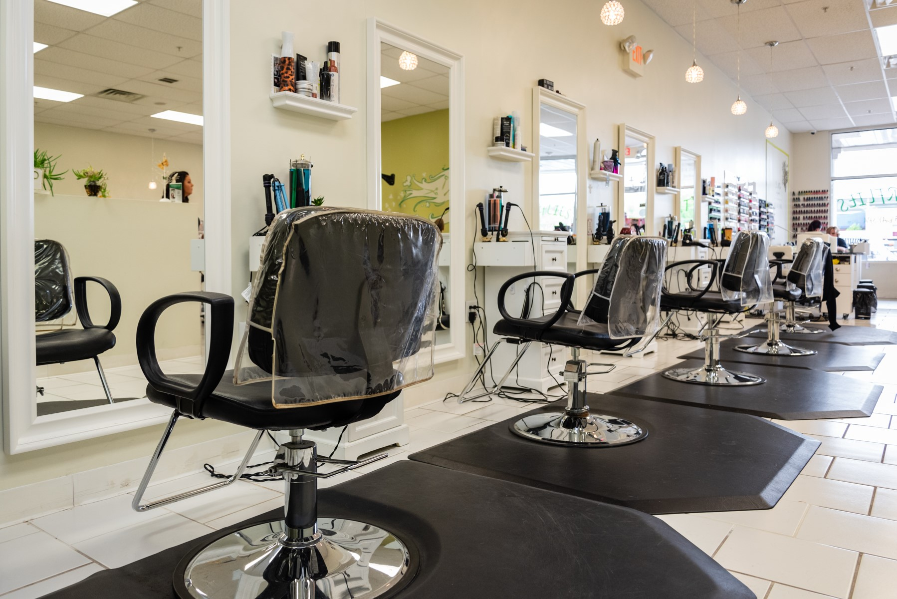 Photo of a salon with barber chairs covered with plastic and a wall of nail polish in Central, New Jersey.