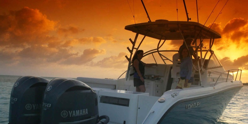 Image of a Charter Boat in NJ with two woman and a man on it with a golden sunset reflecting on the water.