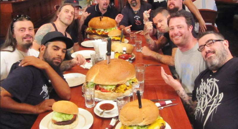 Photo of a bunch of guys at a table with huge burgers on the table as part of the Clinton Station Diner's unique challenge where you can win money if you eat their massive burgers.