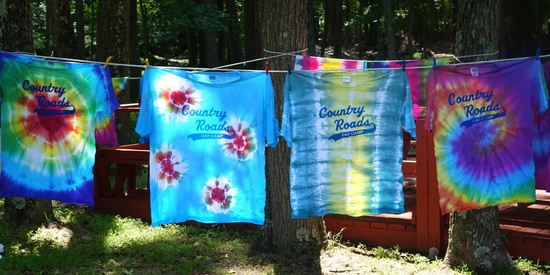 Image of four tye die tee shirts with Country Roads Day Camps logo on the front hanging on a clothes line.
