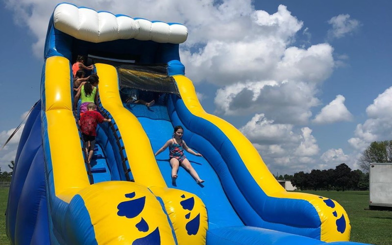 Photo of a little girl sliding down a large blue and yellow inflatable slide with kids walking up the stairs.