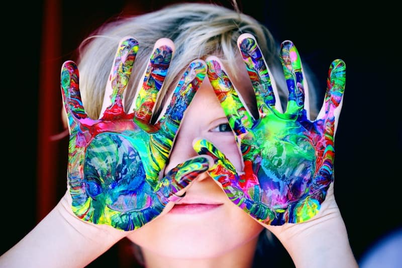 Photo of a kid holding his palms up with a bunch of nicely colored paints completely covering the bottom of his hands. Finger painting is a fun thing to do for kids.