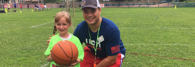 Image of a girl holding a basketball standing on a soccerfield with one of the staff at Fundamentals Day Camp.