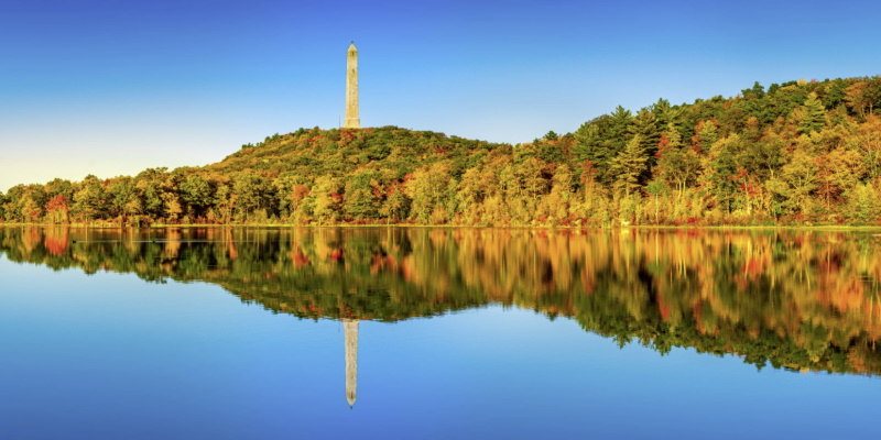 Image of the lake and autumn trees in the background reflecting in the water at High Point State Park as a fun place to bring kids in NJ