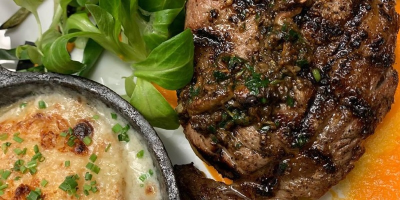 Image a romantic steak and potatoes meal with green basil leaves.=