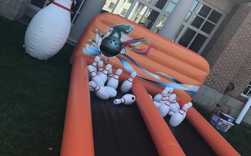 Image of a orange inflatable bowling game with two lanes and pins knocked down