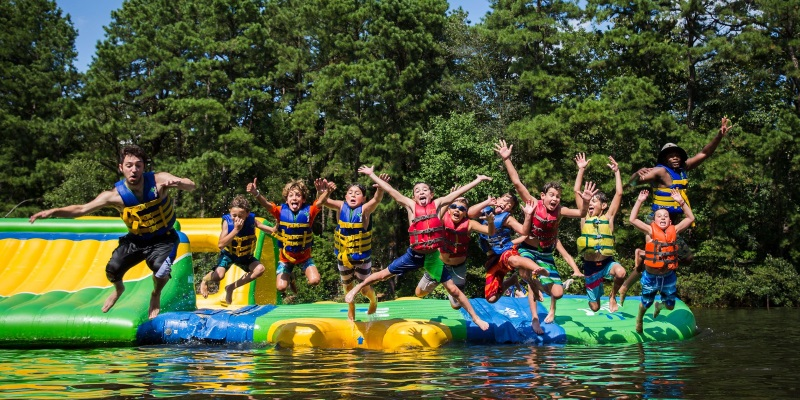 Photo a bunch of children jumping into a lake off a mid lake platform all wearing life vests.