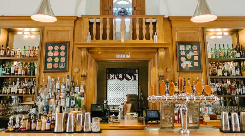 Image of the bar at Jockey Hollow Bar and Kitchen with various bottles of alcohol.=