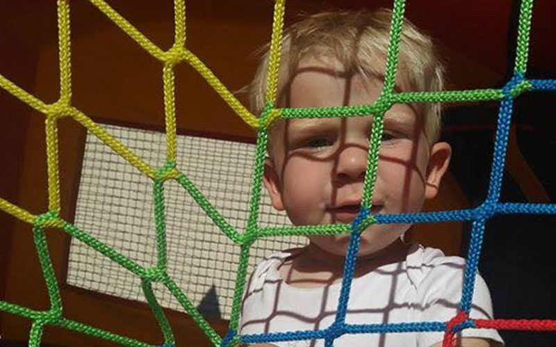 Photo of a blond boylooking through a yellow blue and green safety net on a inflatable bounce house. Finger painting is a fun thing to do for kids.