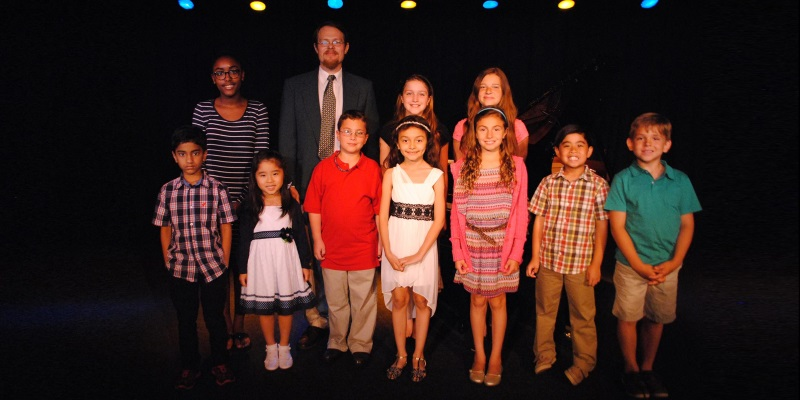 Image of a number of children standing on stage with a black background and a theater teacher next to them at MTC day camp in Marlton, New Jersey.