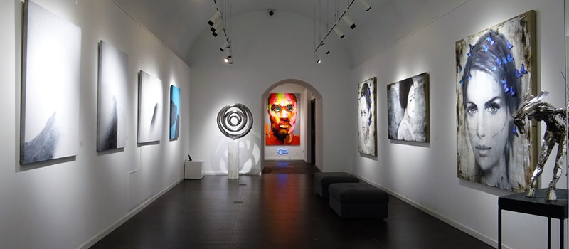Photo of an art museum in NJ with 8 paintings on the wall and 3 sculptures