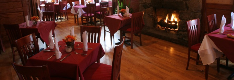 Photo of the dining area of Northwood Inn with a fireplace and red table cloths