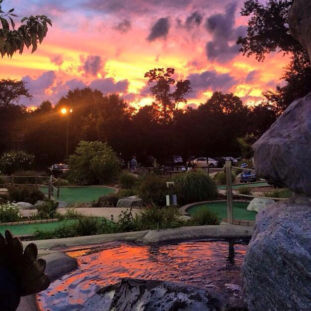 A sunset photo of a waterfall and 4 holes at the Paramus Mini Golf Course in located in North Jersey