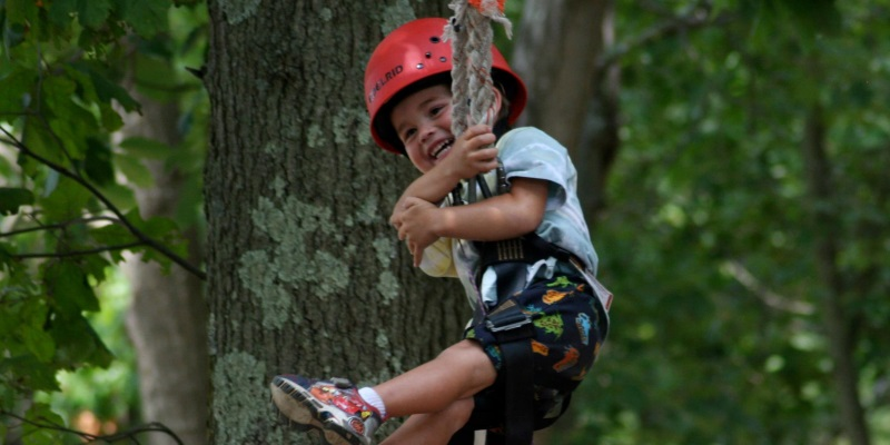 Photo a little boy swinging from a tree in a harness with a red helmet on at a day camp in New Jersey.