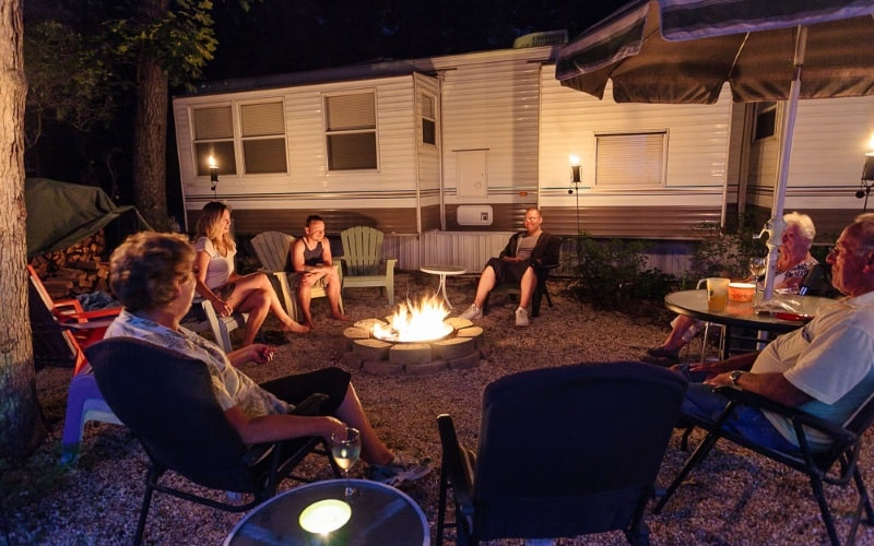 A image of people sitting around a campfire relaxing at night with a RV behind them while camping at Pine Haven