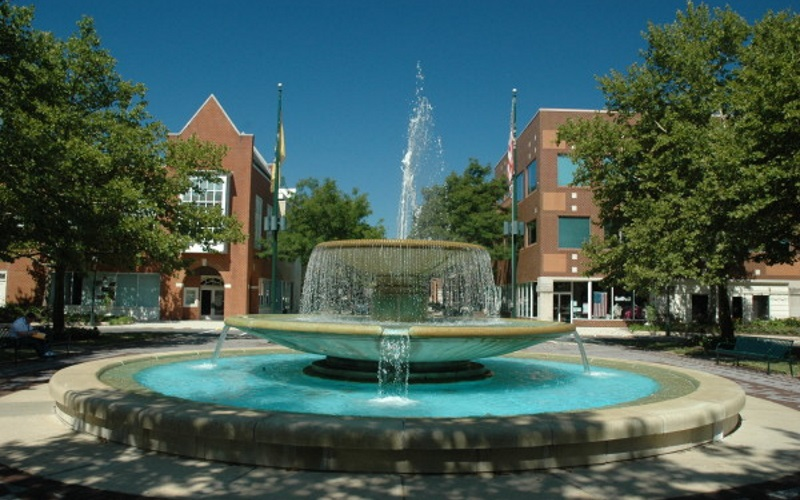 Photo of a fountain in the middle of the Princeton Forrestal Village in Mercer County NJ with red brick buildings in the back.