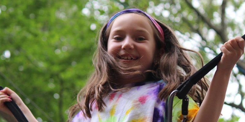 Image of a girl in a tye dye shirt on a trampoline at the Rolling Hills day camp in Freehold, NJ.