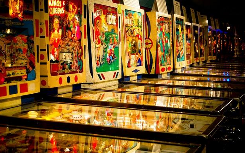 Image of a row of brightly lit up classic and vintage pinball machines.