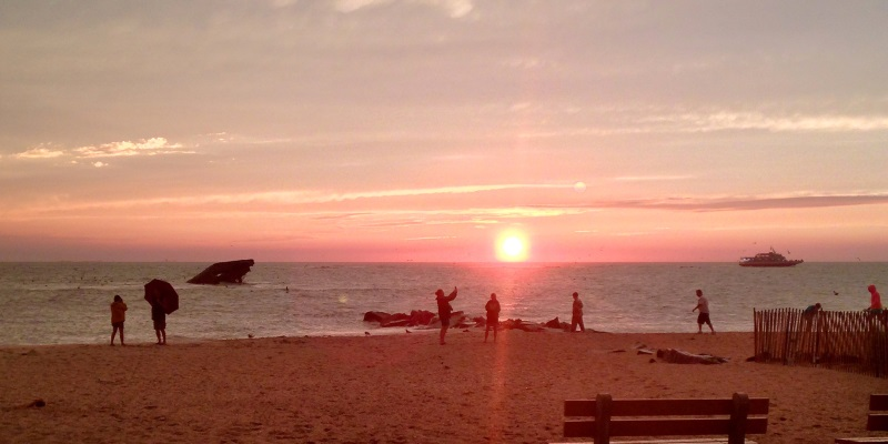 Photo of a sunset at Sunset Beach in Cape May New Jersey with people walking on the sand.