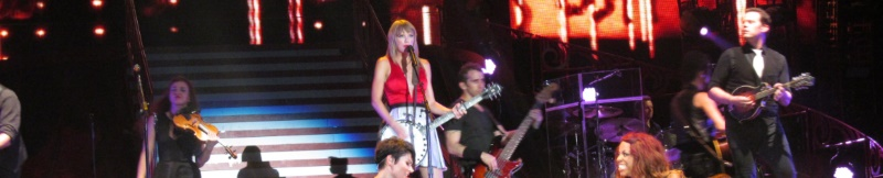 Taylor Swift on stage playing a concert in New Jersey with a violinist and two guitar players