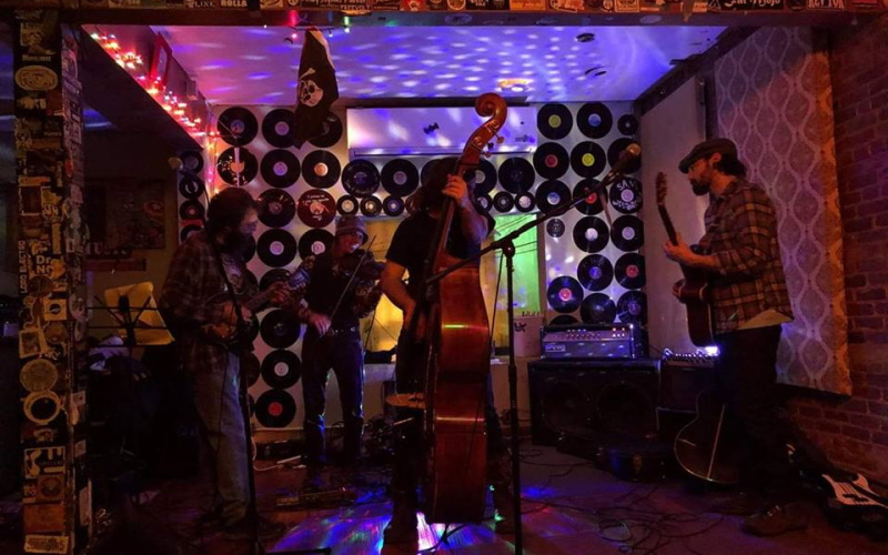 Photo of a band playing at The Saint in Asbury with a stand up bass in front and records hanging on the wall with colorful lights illuminating the wall.