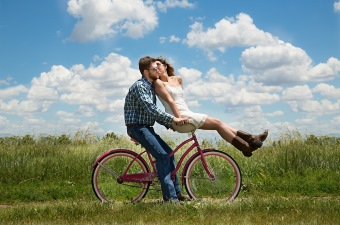 Image of Two People Kissing on a Bicycle in a Grassy Field as an example of a romantic New Jersey date idea