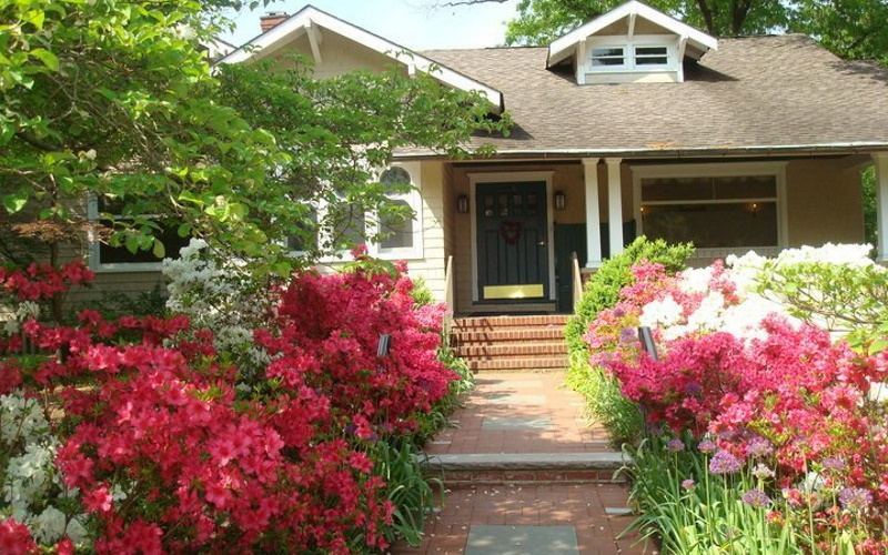 Image of a cottage with blooming red and pink flowers along the walk way