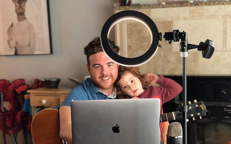 Image of a man in a blue shirt with a child and a guitar on his lap in front of a macbook and lighting set up.