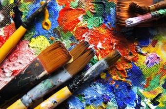 Image of paint brushes in multicolored paints showing art classes as a way to learn in NJ