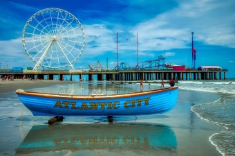 Image of the Ferris Wheel and Atlantic City Boardwalk with a small row boat on beach sand in the front