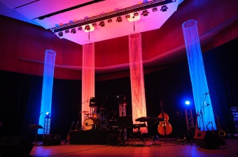 Image of a concert hall lit up with blue and pink lights where one may request party rentals in NJ