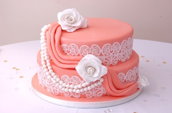 Image of a pink cake with lace design and roses detail showing the food party services available in NJ