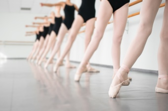 Image of ballerinas with their toes pointed standing at a bar during a dance class in NJ