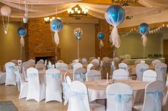 Image of tables set up with white linens and balloons showing a special occasion in NJ