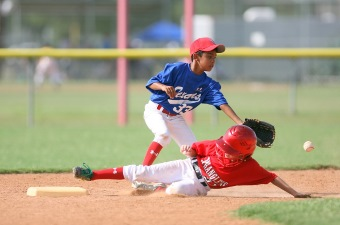 Image of two boys playing baseball with one running over the base as one of the sports centers in NJ