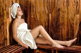 Image of a woman wearing a towel and sitting in a sauna as a honeymoon destination in NJ