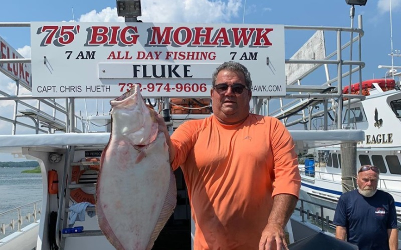 Image of a happy customer after fishing for fluke
