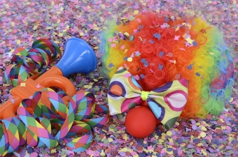 Image of a wig and clown nose laying in confetti showing a New York birthday party idea