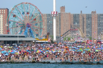 Photo of people on the Coney Island NY boardwalk with a ferris wheel and roller coaster in the background showing fun that goes beyond NJ