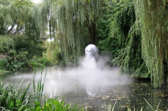Image of a statue on water surrounded by mist and trees at Grounds for Sculpture at a fun NJ attraction