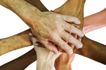 Image of multiple people putting their hands together to display corporate team building and bonding in NJ
