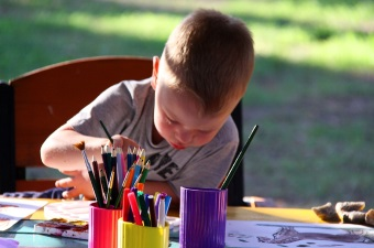 Image of a kid sitting outside at a table using a paintbrush to paint on a canvas