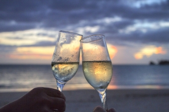 Image of a romantic wedding toast with two champagne glasses half full with a beach (ocean shoreline) behind them at dusk