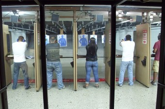 image of three people shooting guns at human paper targets at a shooting range, which looks like a really cool thing to do in NJ