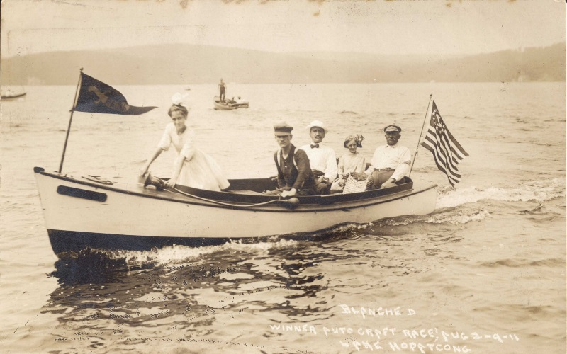 Old photo of people riding a boat on the lake.