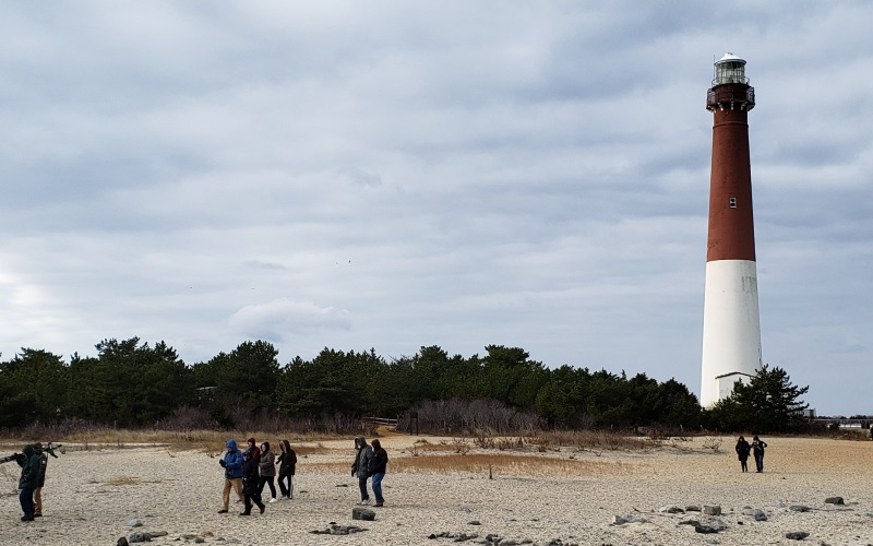 image of the barnagate light house with people on the beach